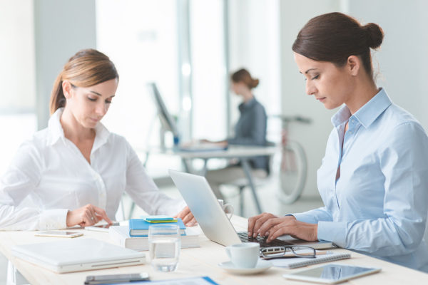 Successful confident business women working at office desk, efficiency and professionalism concept